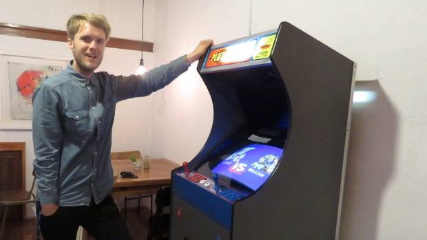 Dale Brimblecombe with a restored arcade game at Wolf at the Door cafe in Dunedin's Carroll St.
