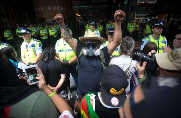 A masked protester stands in front of a police line at SkyCity.