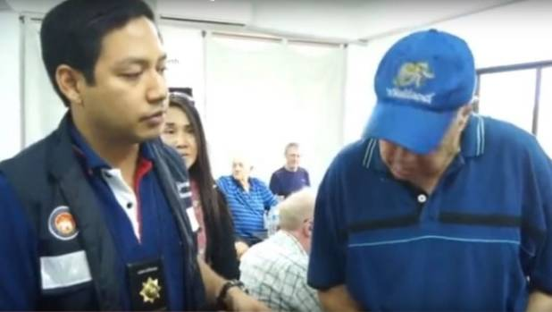 An elderly bridge player is questioned by a Thai policeman at a Jomtien & Pattaya Bridge Club meeting in Pattaya.