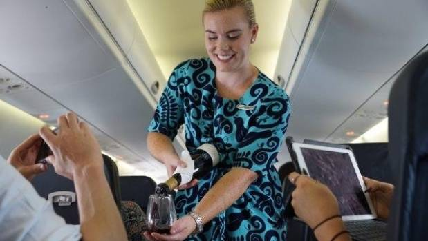An Air New Zealand flight attendant pours a glass of wine on the first 'Wine Flight', which paired award-winning wines ...