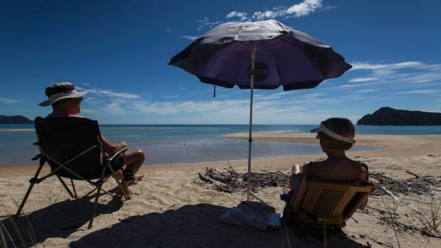 Kevin and Heather Brown relax on a beach in Awaroa Inlet.