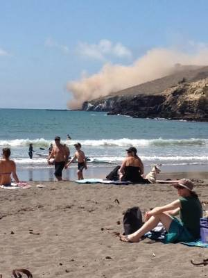 People watch on as huge dust clouds rise have Talyor's Mistake, where a cliff collapsed in Sunday's earthquake.