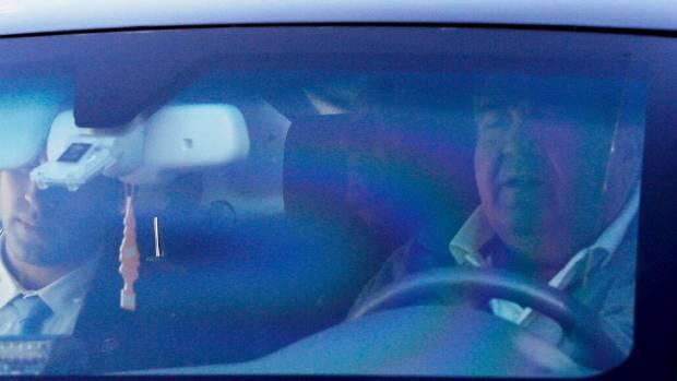 Former Israeli Prime Minister Ehud Olmert (right) is seen inside a car as he leaves his house in Jerusalem.