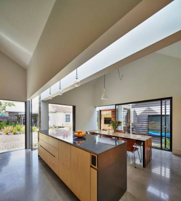 Natural light floods the kitchen from the glazed linking element that runs parallel to the island.