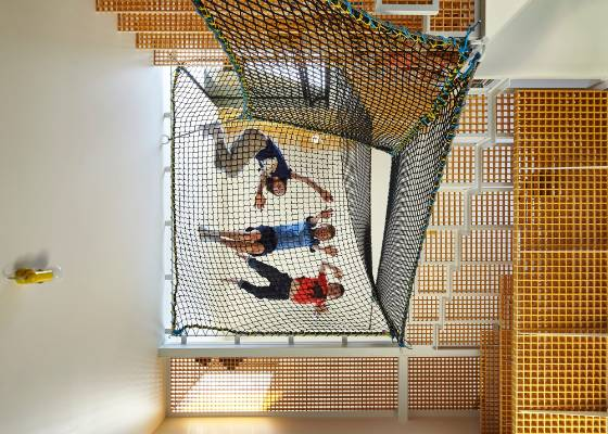 Children enjoy clambering over the net suspended between the stairs and the walls.