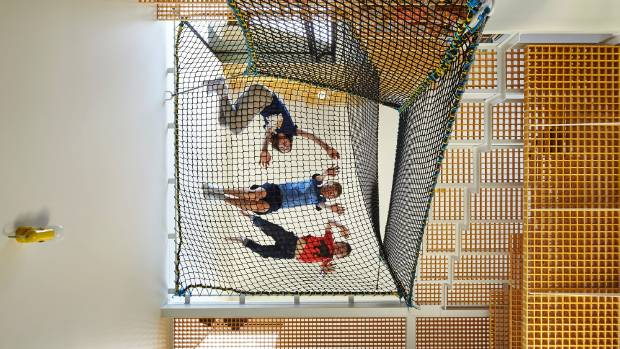 Children enjoy clambering over the net that is suspended between the stairs and the wall in the tall studio.
