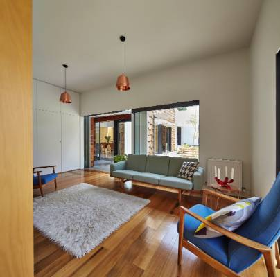 Mid-century Modern furniture and copper light pendants enliven the living room.