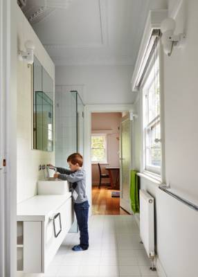 A freestanding wall separates the family bathroom from the laundry on the other side.