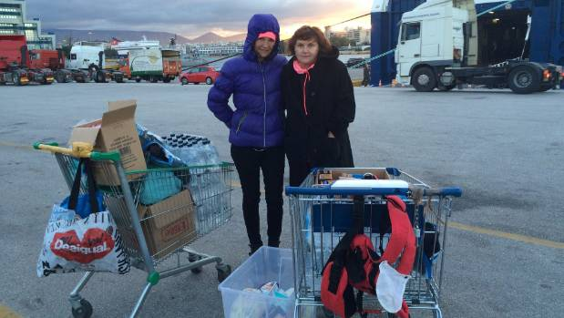 Judy Boyle and Kristina Alicia of Belgium wait with shopping trolleys full of goods donated for incoming refugees.