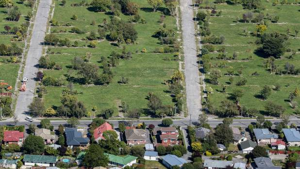 A street marks the border between the red zone, where all homes have been cleared, and the green zone where houses ...