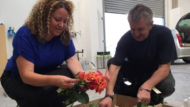 Michelle Whitaker and Evan Smith prepare flowers for Monday's River of Flowers.