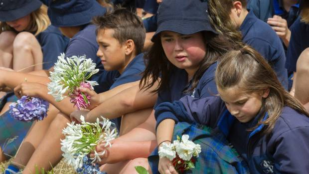 Students from Shirley Intermediate School observe two minutes of silence at a River of Flowers ceremony on the banks of ...