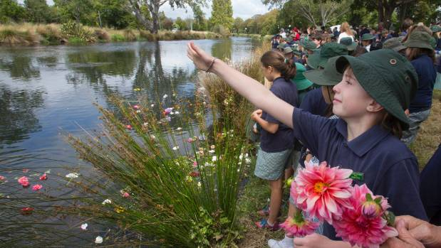 Local school children throw flowers into the Avon to mark the fifth anniversary of the deadly February 22, 2011 earthquake.
