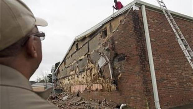 Reverend Frederick Matthews watches Eugene Trice, 38, knock down bricks from the wall of the New Mount Bethel Baptist ...