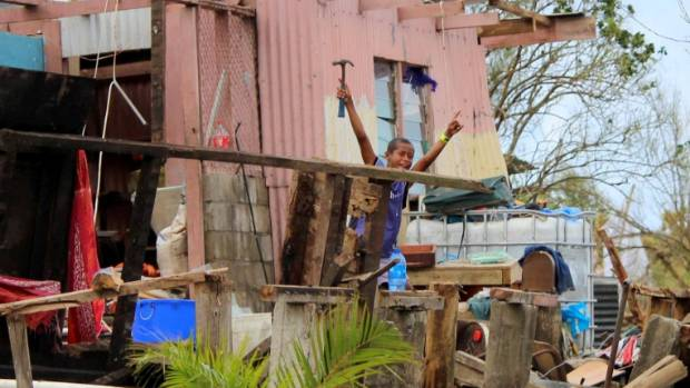 A young boy shows optimism despite the damage to the family house in the Rakiraki district from Tropical Cyclone Winston.
