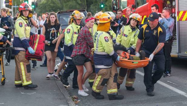 Emergency services and members of the public carry an injured person to an ambulance after a balcony collapsed near a ...