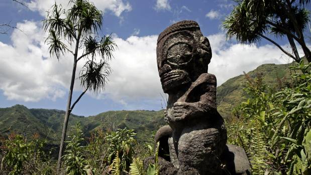 Visit one of the historic tiki sculptures such as this one on Hiva Oa island, Marquesas islands.