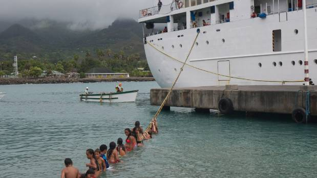Local children swinging on Aranui 3 lines on Ua Pou island, Marquesas. The Aranui shipping company has been operating a ...