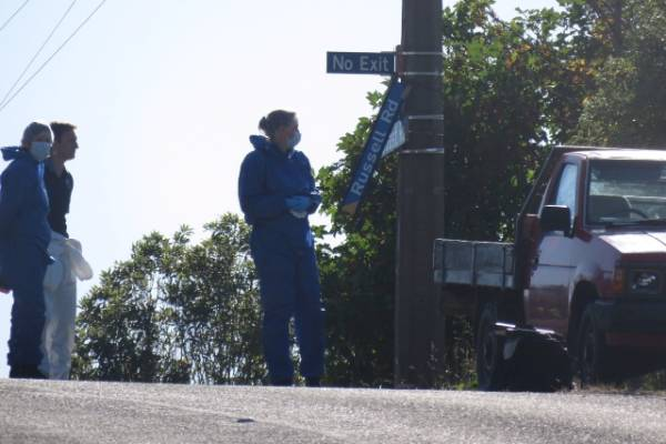 Investigators appear to be concentrating on a ute at the front of the dead woman's property, as well as a broken window ...