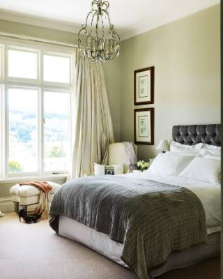 The restful master bedroom has a grey silk velvet headboard designed by Bridget.