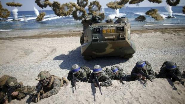 South Korean (blue headbands) and US Marines take positions as amphibious assault vehicles of the South Korean Marine ...