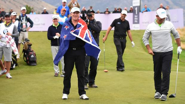 New Zealand Prime Minister John Key wears the New Zealand flag after Ricky Ponting pulls it out on the first tee during ...