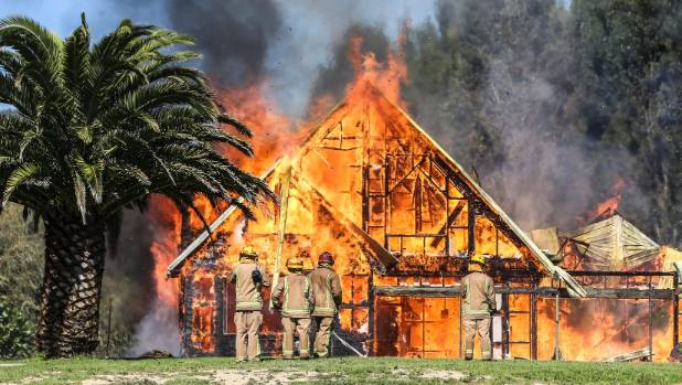 Firefighters burn a Waiheke home that used to belong to Mark Hotchin to the ground.