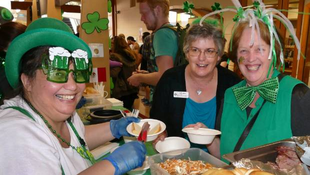 Invercargill City Library customers advisor Catherine Wilson dishes up Irish corn sliders for Debra O'Connor and Chanel ...