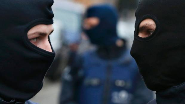 Masked police in Brussels during the raid.