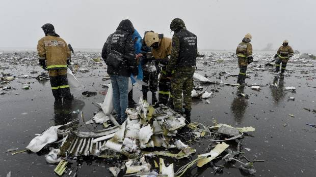 Emergencies Ministry members and investigators examine debris.