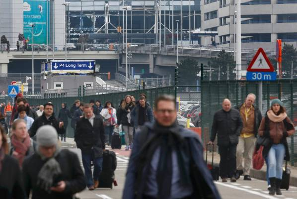 People leave the scene of explosions at Zaventem Airport.