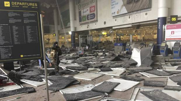 A soldier at Zaventem airport in Brussels after a blast occurred. Ceiling tiles can be seen all over the floor.