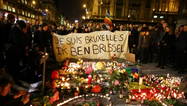 People hold up a banner as a mark of solidarity at the Place de la Bourse following attacks in Brussels, Belgium.