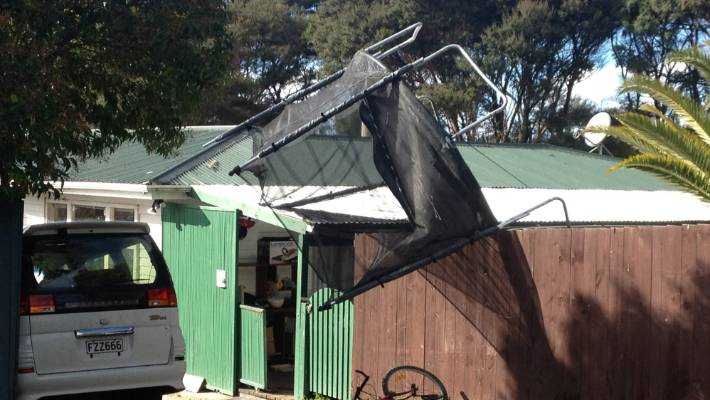 A trampoline smashed through a fence and came to rest on the roof of a house north of Auckland.