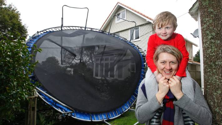 Jacqui Donnell and her son Joshua, 4, in front of the trampoline that was hanging from power lines of their house after a massive storm in Wellington.