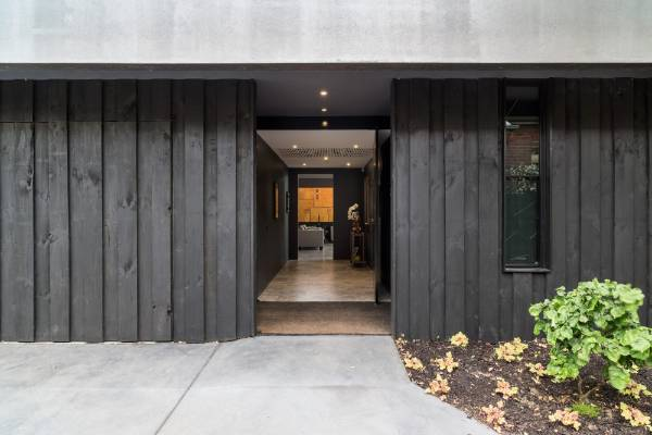The dark-stained vertical siding is a novel use of the traditional plinth board on a fence.