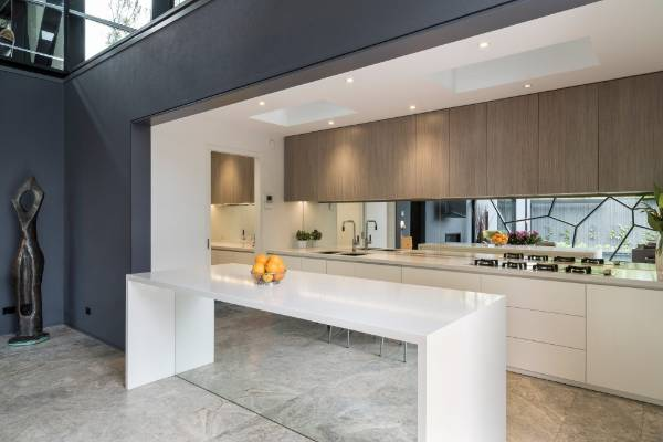 A mirrored splashback and front to the island bounce light back into the room. The cabinetry appears to extend through ...