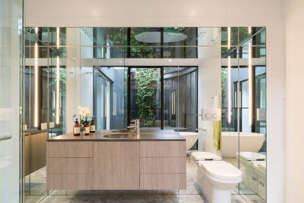 The view outdoors is reflected in the mirrored walls of the ensuite bathroom.