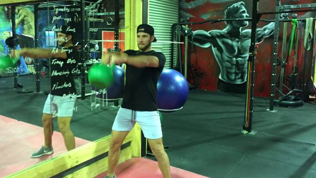 Trainer and gym owner Braden Lee at Industrial Fitness, Queenstown, demonstrates a kettle-ball swing.