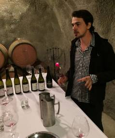 Arthur Robert, cellar door host, tastes wines in the cave at Gibbston Valley Winery.
