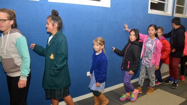 Past and present pupils of Petone Central touch the walls of the revamped classroom block during a dawn blessing ceremony.