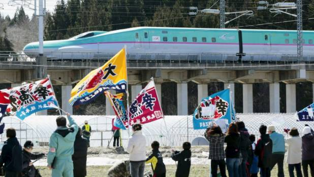 People wave flags as the first train of the new Hokkaido shinkansen, or bullet train, from Tokyo, travels near Kikonai ...