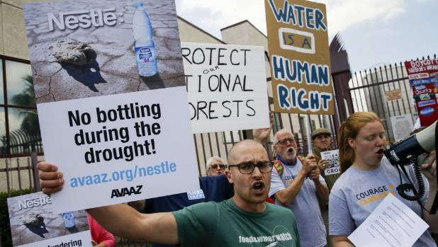 Demonstrators protest against Nestle bottling water during the California drought, outside a Nestle Arrowhead water ...