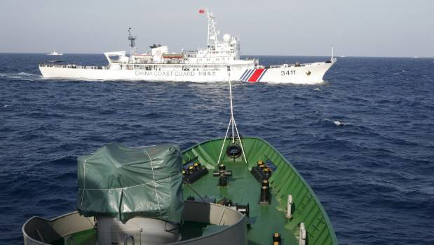A Chinese Coast Guard ship (top) is seen near a Vietnam Marine Guard ship in the South China Sea, about 210km off the ...