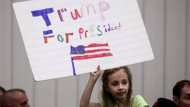A young supporter holds up after US Republican presidential candidate Donald Trump spoke at a campaign event in an ...