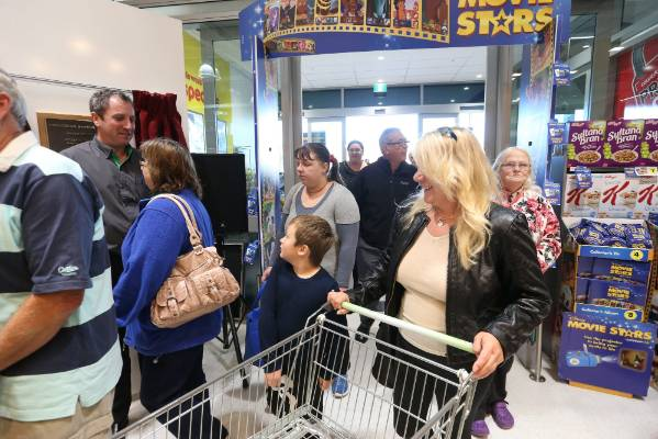 The first customers through the door include Joel Cox, 7, center, with mum Paula Spooner, front right.