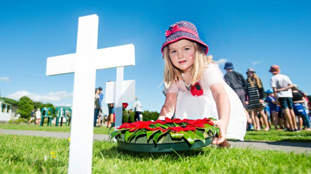 Olive Glasgow, the youngest student at the school, lays the wreath at the cross of the unknown soldier on her first day ...