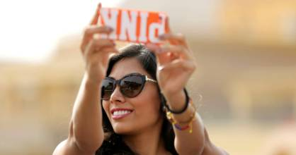A contestant of Miss ECO Universe takes a selfie with pyramids behind, on the outskirts of Cairo.