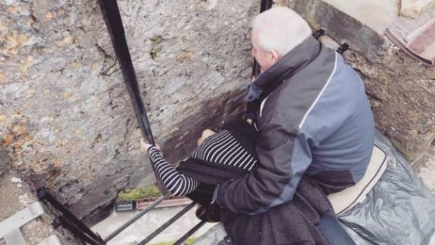 A woman bends over to kiss the Blarney Stone.