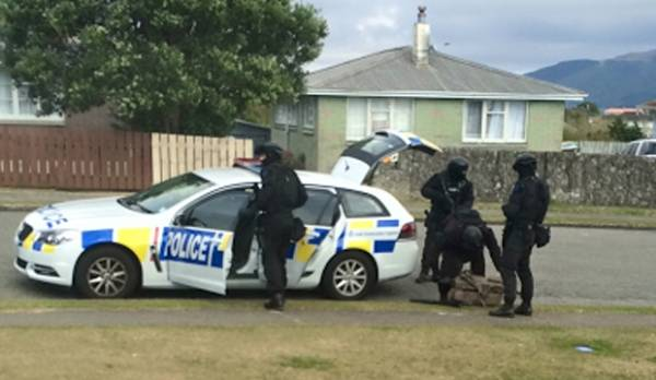 Members of the armed offenders squad hunt for a man believed to have shot a police dog.